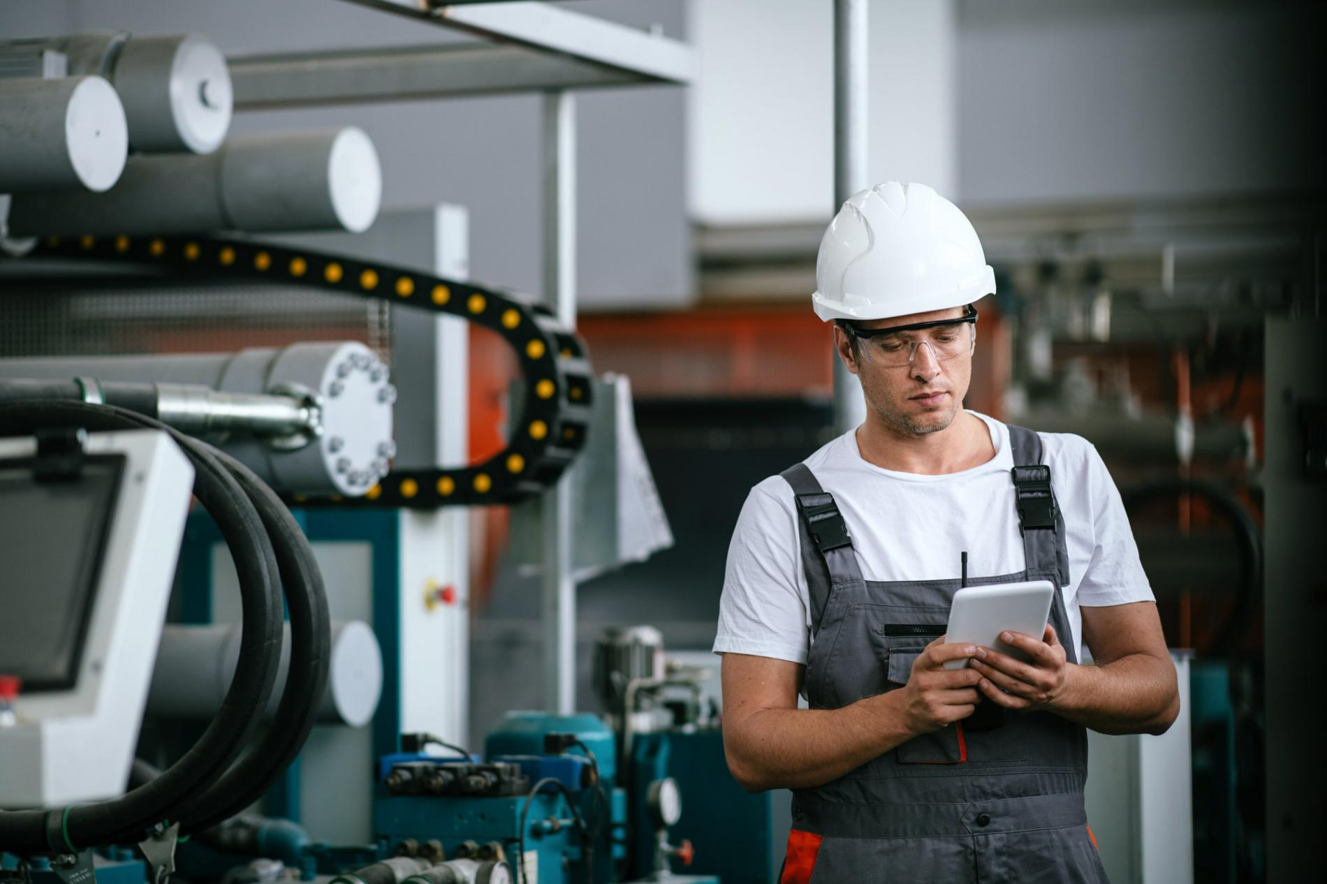 Man standing next to machine, looking at tablet